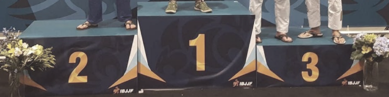 picture of an IBJJF podium with feet on it